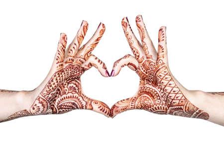 Manos de mujer con henna haciendo el gesto de corazón aislado sobre fondo blanco con trazado de recorte