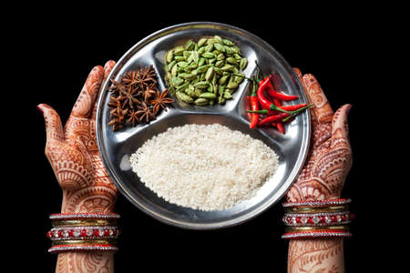 Woman hands with henna holding plate with rice and spices isolated on black background