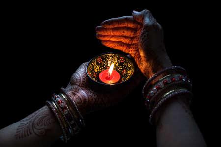 Manos de mujer con celebración henna velas aisladas sobre fondo negro con trazado de recorte