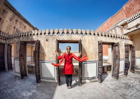 Woman in red dress with scarf opening the door in Hawa Mahal, Rajasthan, India