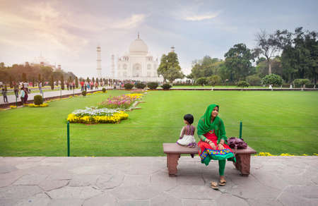 febuary: AGRA, UTTAR PRADESH, INDIA - FEBUARY 24, 2015: Indian woman with her daughter sitting on the bench in the garden of Taj Mahal complex