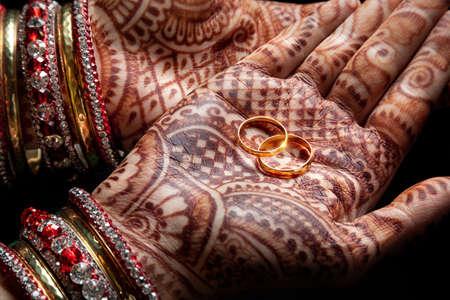 mariage: mains de femme au henné contenant deux anneaux de mariage d'or sur fond noir Banque d'images