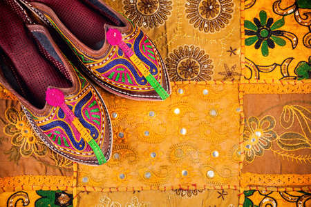 Colorful ethnic shoes on yellow Rajasthan cushion cover on flea market in India