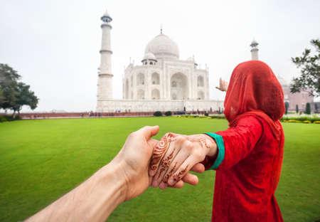 persona viajando: Mujer en traje rojo indio que sostiene a su amiga con la mano y apuntando al Taj Mahal en Agra, Uttar Pradesh, India