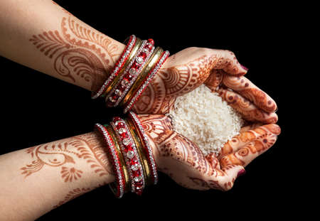 indian cooking: Woman hands with henna holding rice isolated on black background with clipping path Stock Photo