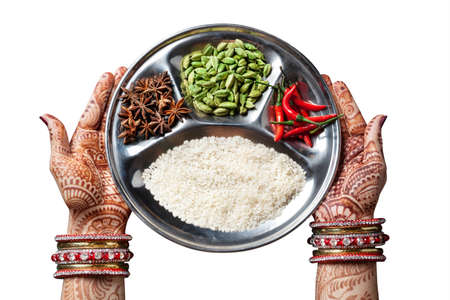 indian spice: Woman hands with henna holding plate with rice and spices isolated on white background with clipping path Stock Photo