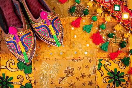Colorful ethnic shoes and gipsy belt on yellow Rajasthan cushion cover on flea market in India Stockfoto