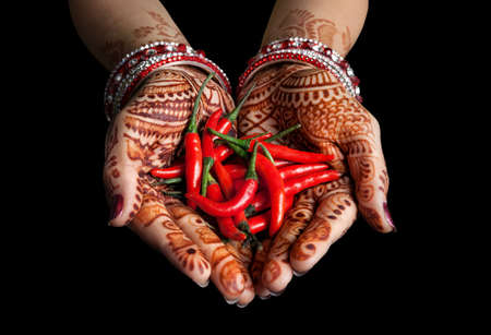 cooking ingredients: Woman hands with henna holding red chili isolated on black background with clipping path