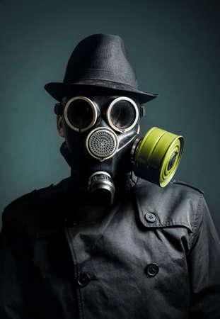 mascara gas: Hombre de la máscara de gas, impermeable y sombrero negro en fondo oscuro