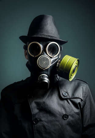 gas mask: Man in gas mask, raincoat and black hat at dark background