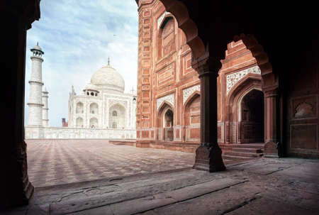 arch: Taj Mahal tomb and mosque in the arch at blue sky in Agra, Uttar Pradesh, India