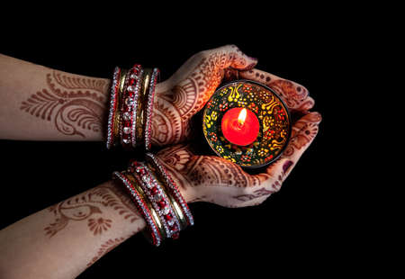 paz interior: Manos de mujer con celebración henna velas aisladas sobre fondo negro con trazado de recorte