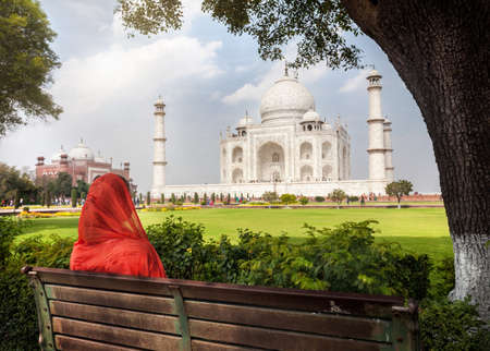 taj: Woman in red scarf sitting on the bench in the shadow and looking at Taj Mahal in Agra, Uttar Pradesh, India