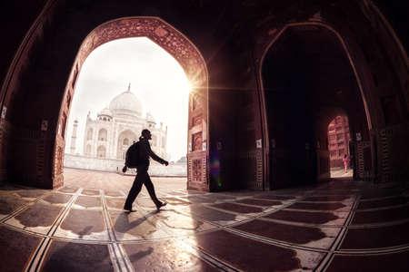 Toeristische met rugzak wandelen in de moskee boog in de buurt van Taj Mahal in Agra, Uttar Pradesh, India