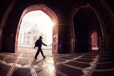 Tourist with backpack walking in the mosque arch near Taj Mahal in Agra, Uttar Pradesh, India Stok Fotoğraf