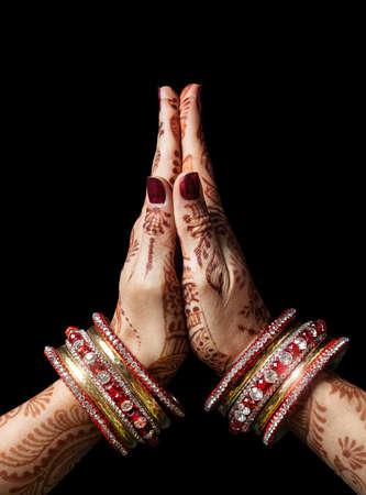 Woman hands with henna in Namaste mudra on black background Standard-Bild