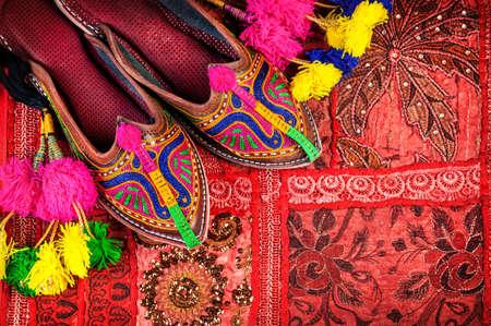 Kleurrijke etnische schoenen en camel decoraties op rode Rajasthan kussenhoes op de rommelmarkt in India