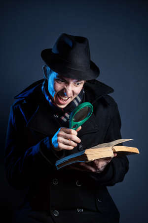 Emotional man in black hat with magnifier glass reading the old book at dark background Standard-Bild