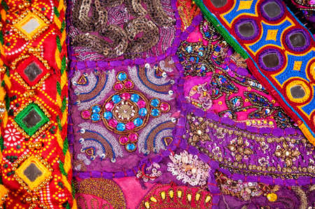 fabric patterns: Colorful ethnic Rajasthan cushion cover and belts with mirrors on flea market in India