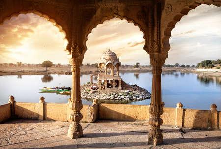 Bogen en de tempel in Gadi Sagar meer bij zonsondergang hemel in Jaisalmer, Rajasthan, India Redactioneel