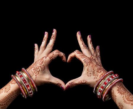 Vrouw handen met henna doen hart gebaar op een zwarte achtergrond met het knippen van weg Stockfoto