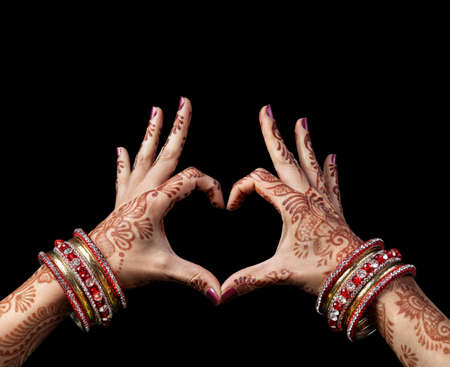 Woman hands with henna doing heart gesture isolated on black background with clipping path Stock Photo