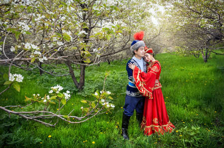 kazakh: Couple in Kazakh costume in Spring Blooming apple garden of Almaty, Kazakhstan, Central Asia