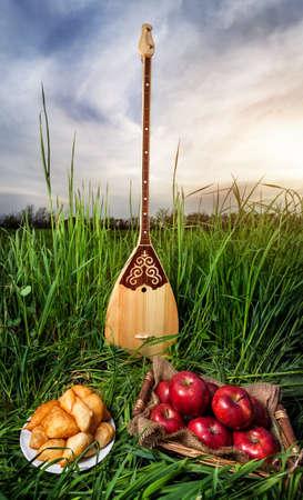 cuisine entertainment: Dombra Kazakh instrument, apples and baursak dish on the grass at sunset sky Stock Photo