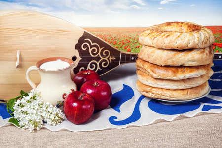 cuisine entertainment: Dombra Kazakh instrument, apples, milk and bread lepeshka on the table at poppy flower field background