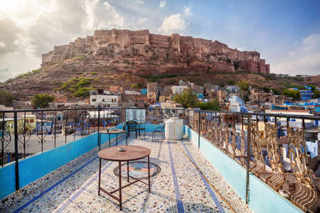 hill of the king: Rooftop cafe with view to Mehrangarh fort on the hill at cloudy sky in Jodhpur Blue city, Rajasthan, India Stock Photo