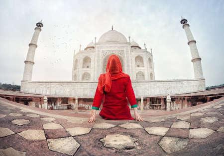 床に座って、アグラ、ウッタルプラデーシュ州、インドのタージ ・ マハルを見る赤い衣裳をつけた女