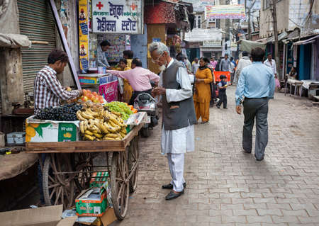 AGRA, UTTAR PRADESH, INDIA - FEBUARY 24, 2015: Muslim man buying fruits from the seller on the Taj Ganj Street Редакционное