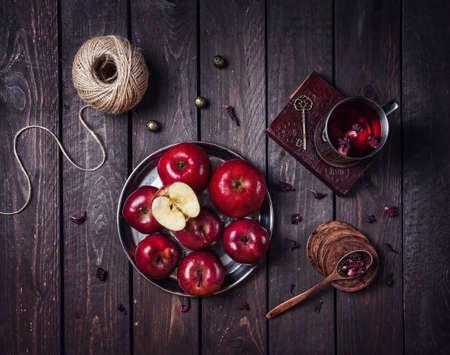 暗い背景の木にある古い本をハイビスカス ティーとプレートとマグカップ赤りんご