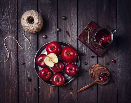 Red apples on the plate and mug with hibiscus tea on the old book at dark wooden background 免版税图像