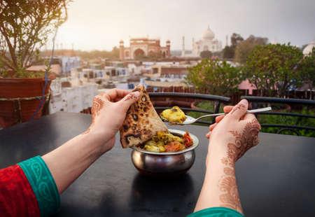 food on table: Donna che mangia cibo tradizionale indiano in ristorante panoramico con vista Taj Mahal ad Agra, Uttar Pradesh, India
