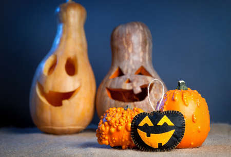 funny fruit: Carved pumpkins and handmade toy from felt on the sackcloth at Halloween party Stock Photo