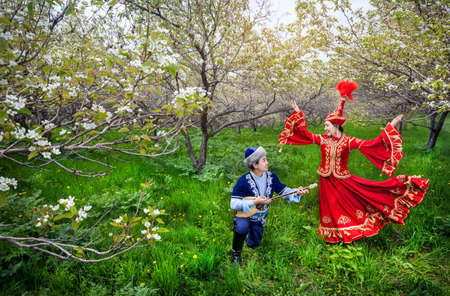 folk village: Kazakh woman dancing in red dress and man playing dombra at Spring Blooming garden in Almaty, Kazakhstan, Central Asia