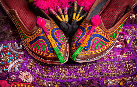 india culture: Colorful ethnic shoes and camel decorations on violet Rajasthan cushion cover on flea market in India