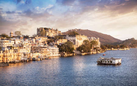 hill of the king: Lake Pichola with City Palace view at cloudy sunset sky in Udaipur, Rajasthan, India Editorial