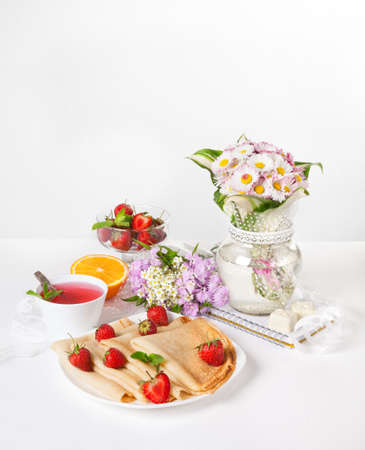 light breakfast: Strawberry, pancakes, orange and hibiscus tea on the table with flower bouquet at breakfast time
