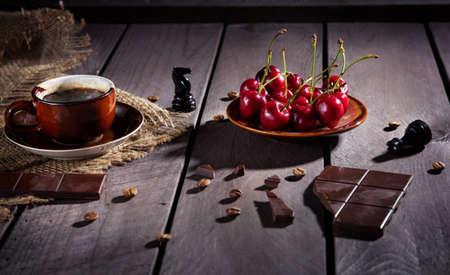 caballo bebe: Taza de café, chocolate negro y cerezas en la mesa de madera con figura de ajedrez negro cercano Foto de archivo