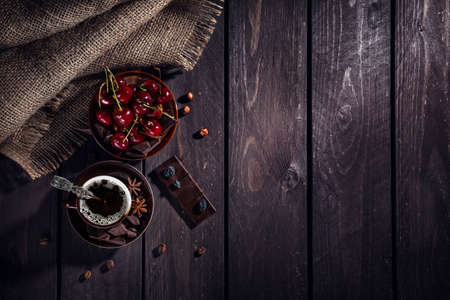 Coffee cup, dark chocolate and cherries on the wooden table 免版税图像