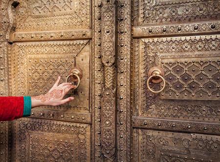 puerta: Mano de la mujer con la pintura de henna abrir la puerta de oro en palacio de la ciudad de Jaipur, Rajasthan, India Foto de archivo