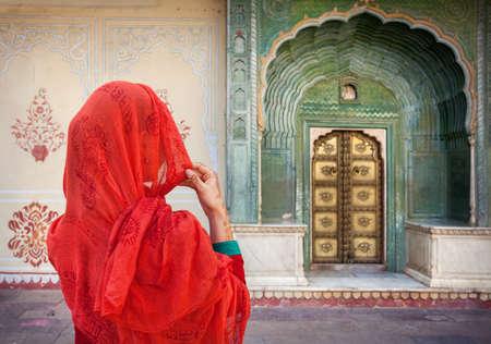 Vrouw in rode sjaal kijken naar groene poort deur in de stad Paleis van Jaipur, Rajasthan, India