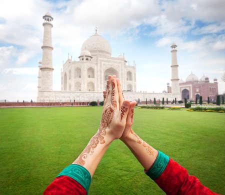 Woman hands with henna painting in Namaste gesture near Taj Mahal in Agra, Uttar Pradesh, India Stock Photo