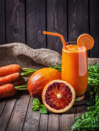 Fresh carrot juice with oranges at wooden background