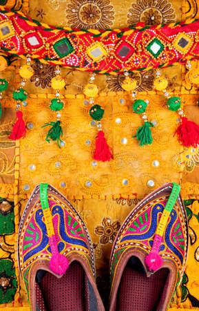 Colorful ethnic shoes and gipsy belt on yellow Rajasthan cushion cover on flea market in India Stock Photo - 40880242