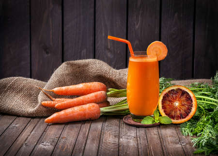Fresh carrot and orange juice with oranges at wooden background Banco de Imagens