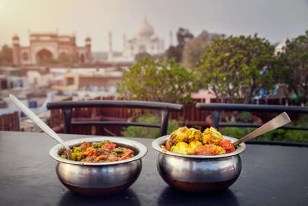 food dish: Aloo Gobi and Sabji Masala Traditional Indian food in metal plates on rooftop restaurant with Taj Mahal view in Agra, Uttar Pradesh, India