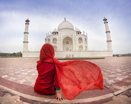 Vrouw in het rood kostuum met flatterende sjaal zitten in de buurt van Taj Mahal in Agra, Uttar Pradesh, India